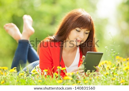 Happy woman with tablet in the park - stock photo