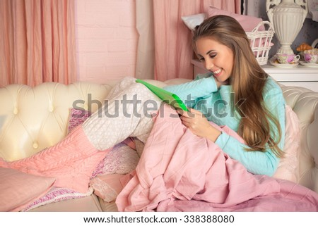 Happy woman with tablet on couch - stock photo