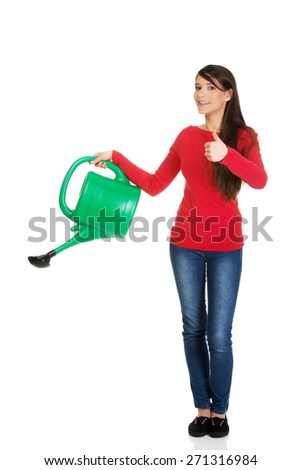 Happy woman with thumbs up holding a watering can. - stock photo