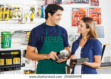 Happy woman with tool set looking at worker swiping credit card in hardware store - stock photo