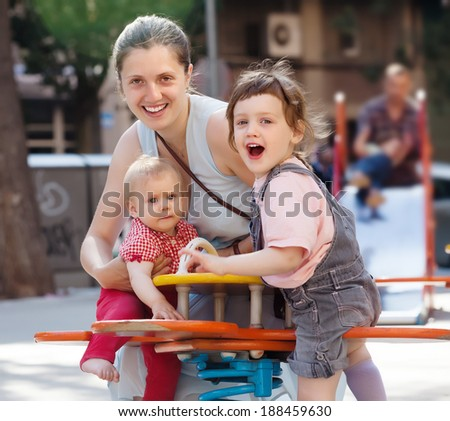 Happy woman with  two children on swings in city playground   - stock photo