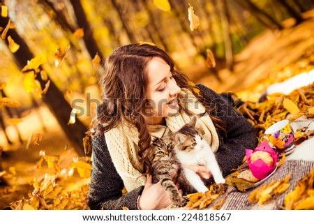 happy woman with two kitties on a plaid at fall forest