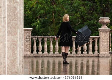 Happy woman with umbrella in the rain - stock photo