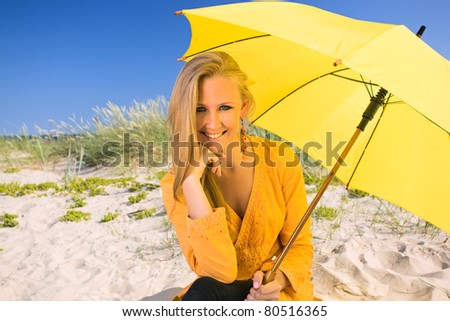 happy woman with umbrella  on a beach. - stock photo