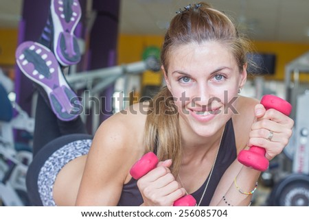 Happy woman with weights in gym - stock photo