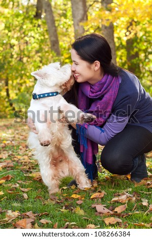 Happy woman with west highland white terrier dog in autumn forest - stock photo