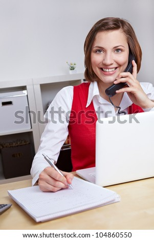 Happy woman working for call center hotline taking notes during a phone call - stock photo