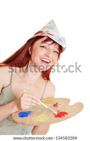 Happy woman working with brush, mixing palette and painter hat - stock photo