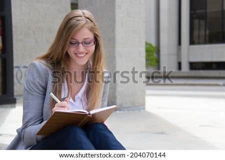 Happy woman writing in her notebook - stock photo