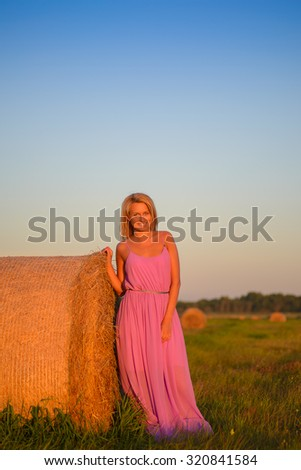 happy womanin pink dress posing  with hay in meadow field at evening time - stock photo