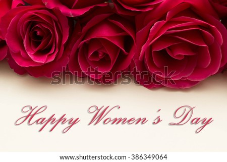 Happy Womans Day March 8th written on white card with red roses