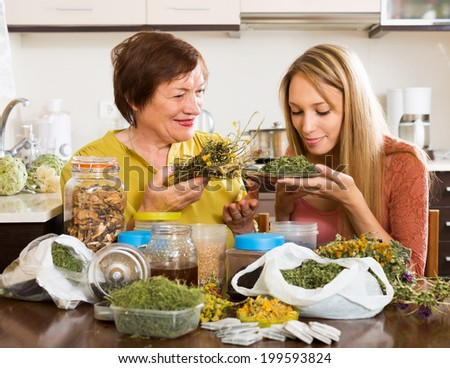 Happy  womans  with medicinal herbs brewing herbal tea - stock photo