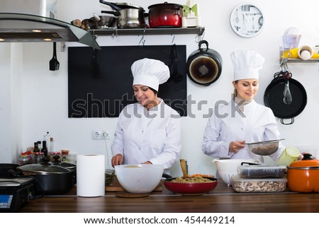 Happy women chefs cooking food at cafe's kitchen - stock photo