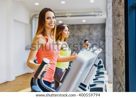 Happy women doing cardio workout at gym - stock photo