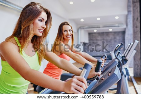 Happy women doing cardio workout on bike at gym - stock photo