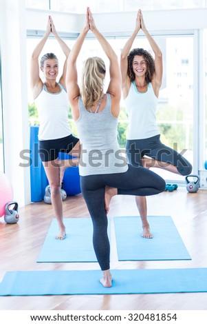 Happy women doing tree pose in fitness studio - stock photo