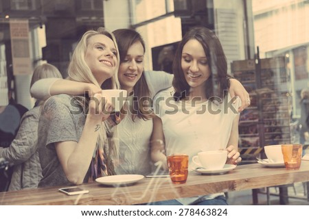 Happy women enjoying a coffee in a cafe in Copenhagen. They are in their twenties, laughing and talking each other. Smart casual clothing. - stock photo