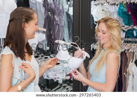 Happy women friends holding lingerie in shopping mall