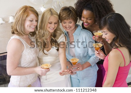 Happy women holding cocktail glass and looking at engagement ring at party - stock photo