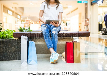 Happy Women holding shopping bags and watching Phone - stock photo