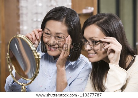 Happy women in shop trying on spectacles