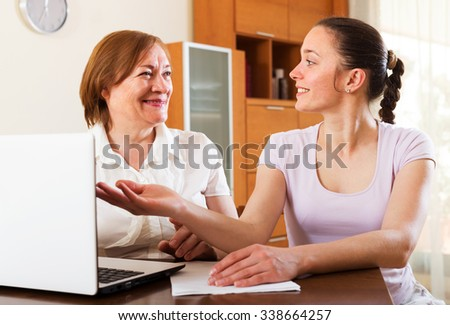 Happy women looking financial documents in laptop at table in home or office interior