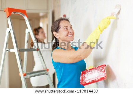 Happy women  making repairs at room