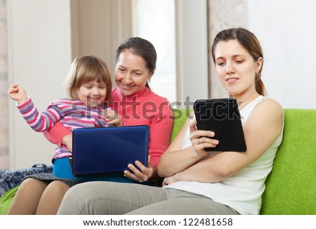 Happy women of three generations sits on the sofa with electronic devices - stock photo