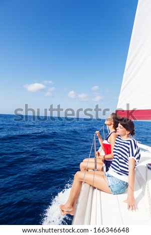 Happy women on the bow of a Sail Boat. Copy space - stock photo
