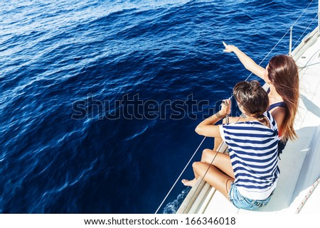Happy women on the bow of a Sail Boat pointing to something. Copy space - stock photo