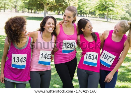 Happy women participating in breast cancer marathon talking at park - stock photo