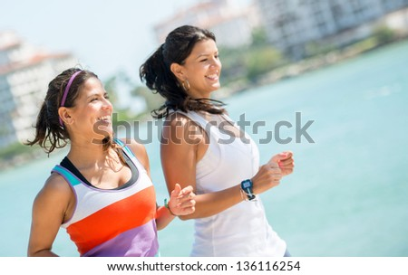 Happy women running outdoors by the beach - fitness concepts