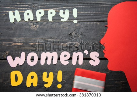 Happy Women's day text laid out homemade colored paper letters with the silhouette red female face ,red gift,present on a dark vintage  wooden table background with  copy space - stock photo