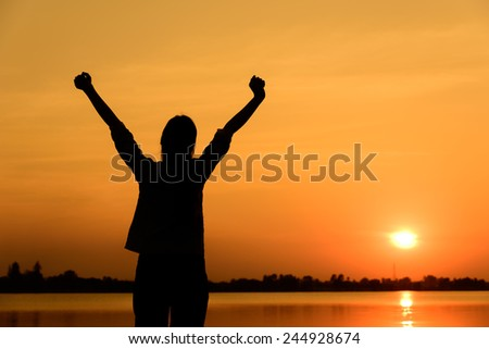 happy women silhouette with sunset and lake