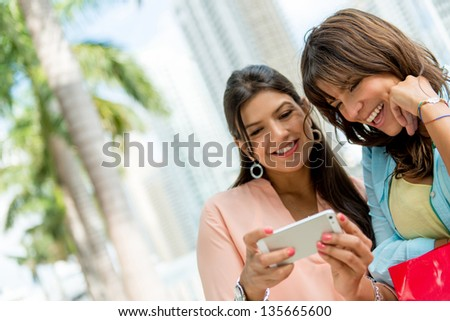 Happy women social networking from a mobile phone - stock photo
