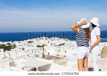 Happy  women standing  on the promenade and looking away, pointing at beautiful cityscape of Mykonos .Copy space - stock photo