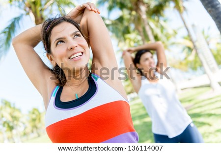 Happy women stretching arms before working out