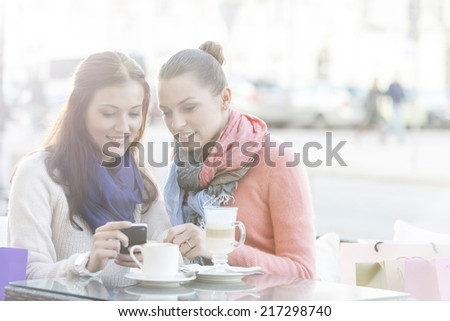 Happy women using cell phone at sidewalk cafe during winter - stock photo