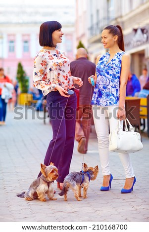 happy women walking the dogs on city street - stock photo