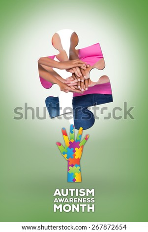 Happy women wearing breast cancer ribbons putting hands together smiling against green vignette - stock photo