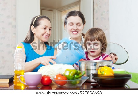 Happy women with child together cooking veggie lunch  in the kitchen  at home
