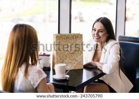 Happy women with coffee cup while keeping company in cafe - stock photo
