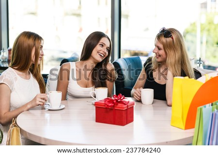 Happy women with coffee cup while looking at camera in cafe - stock photo