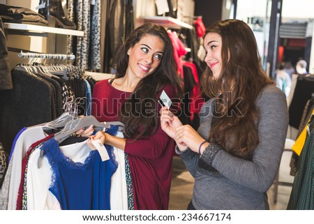 Happy Women with Credit Card in a Clothing Store - stock photo