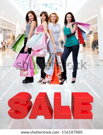 Happy women with shopping bags poses at store with three-dimensional text - stock photo