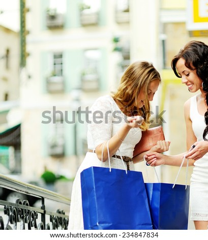 happy women with shopping bags walking downtown - stock photo