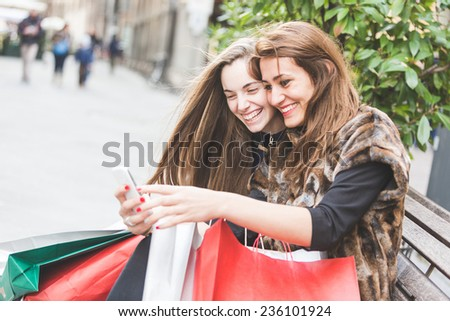Happy Women with Smart Phone and Shopping Bags - stock photo