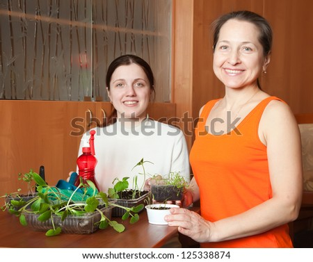 Happy women with various seedlings at home