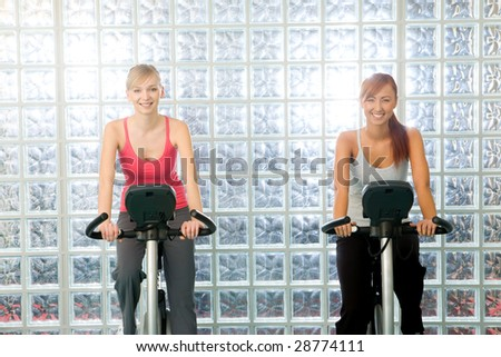 Happy women working out  on bike at gym. They're smiling and looking at camera. Front view. - stock photo