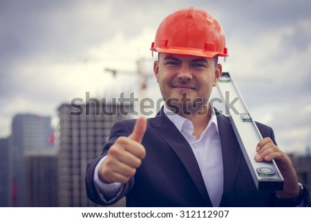 Happy worker architect showing success thumb up on the background of construction
